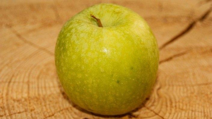 Ein frischer Apfel liegt auf einem Baumstamm
