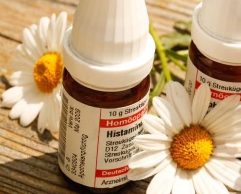 Zwei Fläschen mit Streukügelchen zur homöopathischen Behandlung