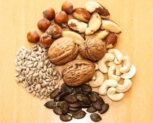 Verschiedene Arten von Nüssen und Kernen liegen auf einem Tisch