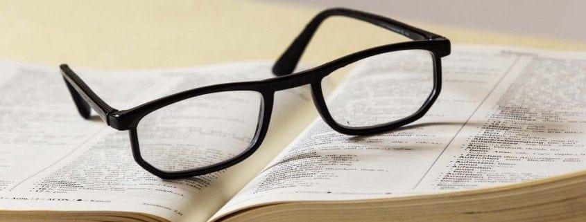 Eine Brille liegt auf einem Fachbuch